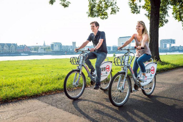 Junges Paar auf KVB Rädern am Rheinufer.