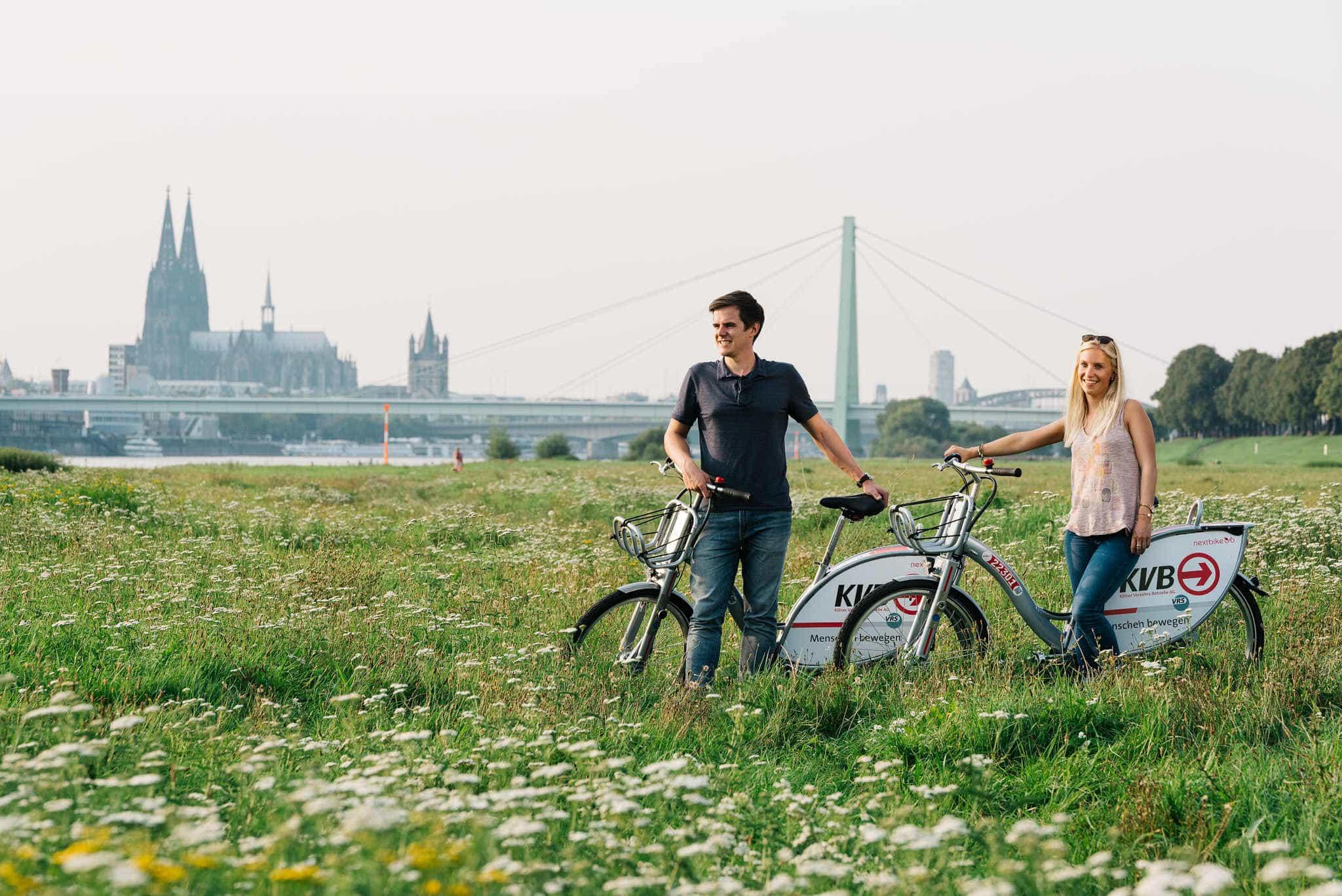 Junges Paar auf den Pollerwiesen mit KVB Rädern.