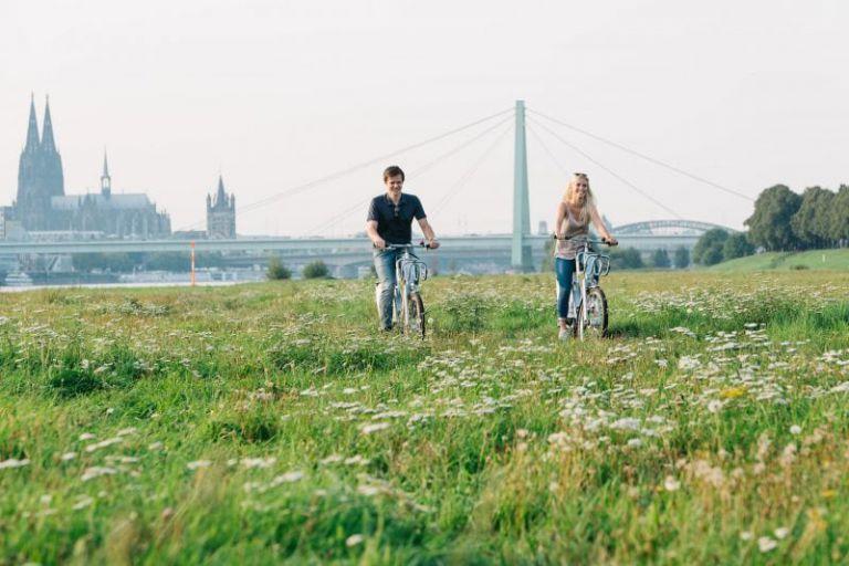 Junges Paar fährt mit KVB Rädern auf Pollerwiesen.