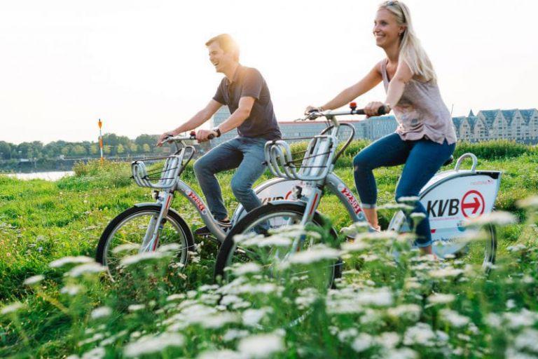 Junges Paar auf KVB Rad im Gegenlicht.