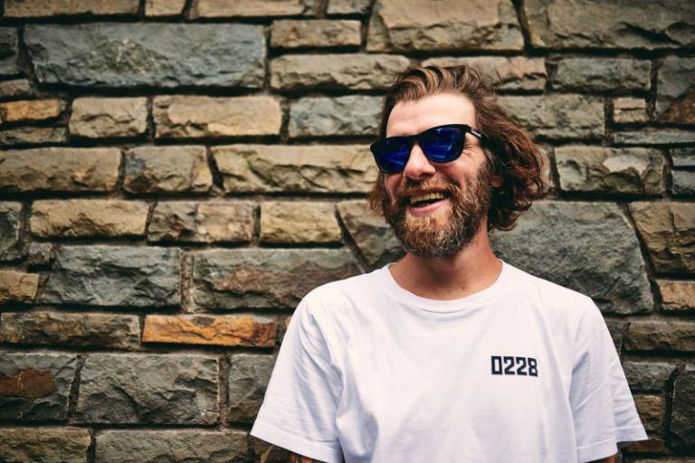 Portrait von Philipp mit Sonnenbrille vor einer Wand.