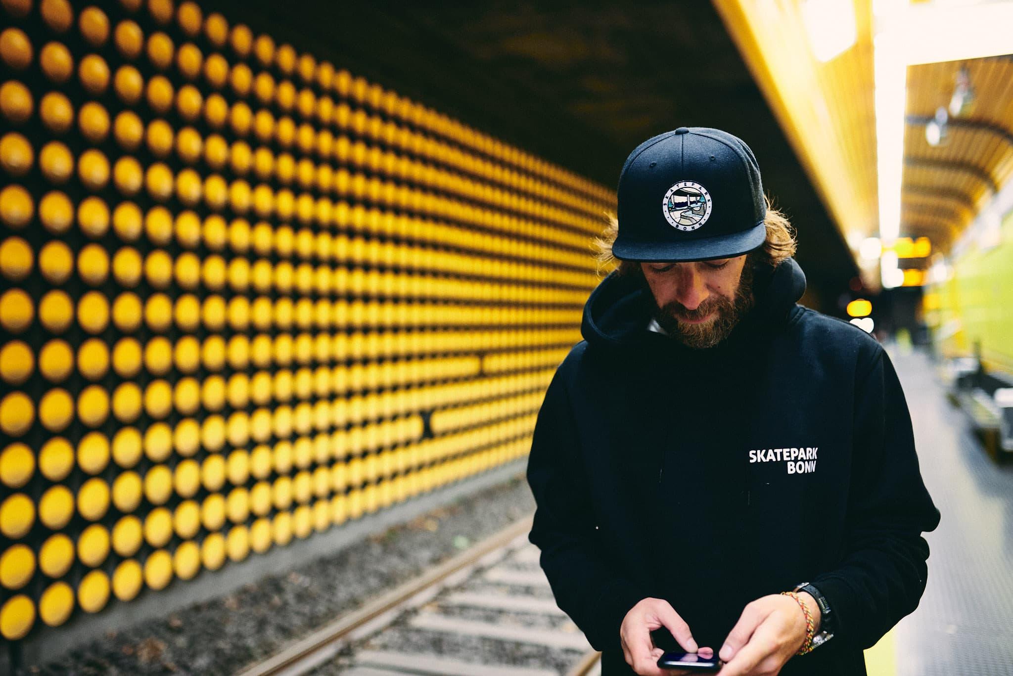 Philipp schaut aufs Handy am Gleis der Haltestelle Rammersdorf.