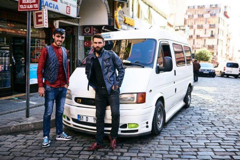 Zwei junge Männer vor ihrem weißen Großraum Taxi posieren für ein Foto.
