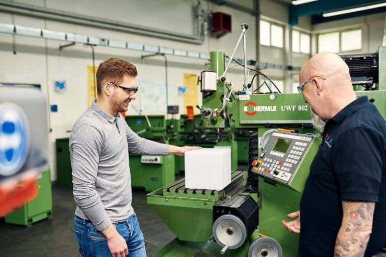 Zwei Männer in einer Werkstatt.