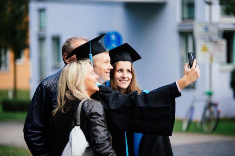 Absolventen machen ein Selfie im Talar.