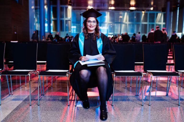 Eine Absolventin in der ersten Stuhlreihe.