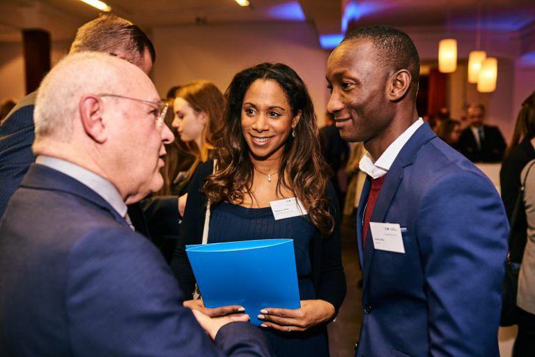 Drei Teilnehmer unterhalten sich auf der Stipendiumsfeier.